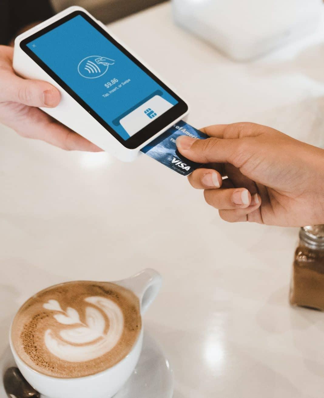 Une personne payant un café à l'aide d'une carte bancaire.